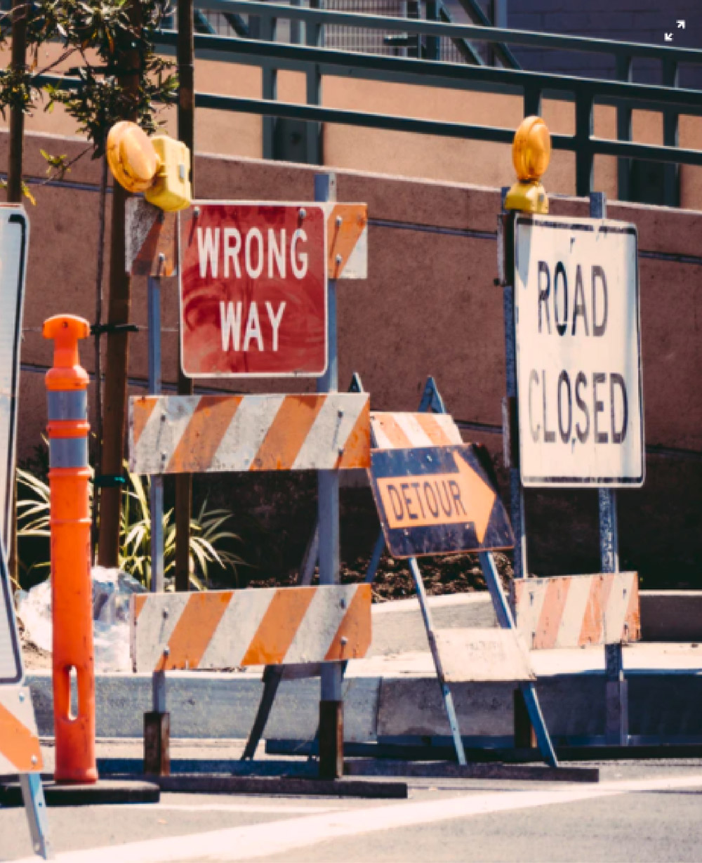 """Construction signage including """"wrong way"""", """"Detour"""", and """"road closed""""."""