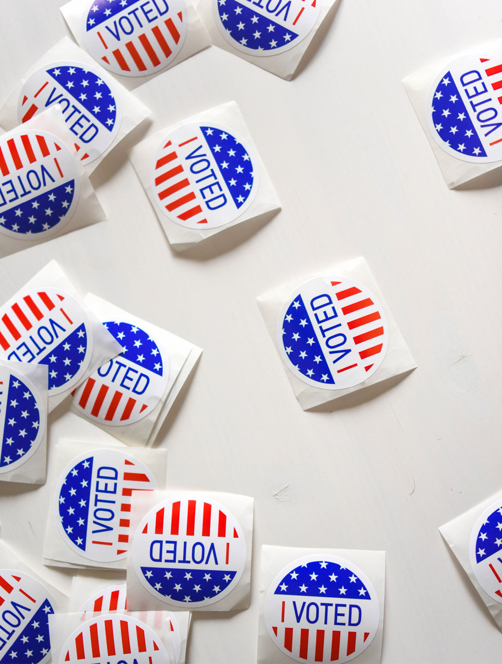 """Paper """"I Voted"""" stickers spread out on a table surface."""