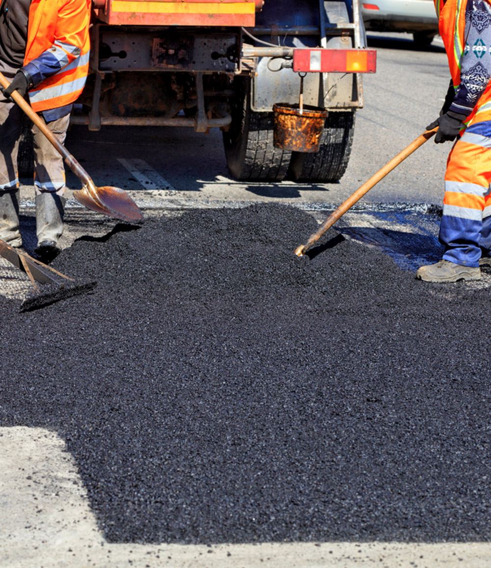 City workers paving a street with asphalt.